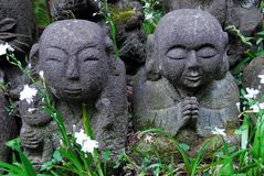 Humorous rakan. Stone rakan , Buddha statues with funny humorous faces partially covered by greenery Stock Images