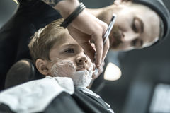 Humorous shaving of little boy. Brutal kid with a shaving foam on the face in the barbershop. He wears a black salon cape. Bearded barber with a tattoo is Stock Image