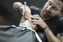 Humorous shaving of little boy. Cute kid with a shaving foam on the face in the barbershop. He wears a black salon cape. Bearded barber with a tattoo is shaving Royalty Free Stock Photos