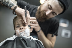 Humorous shaving of little boy. Small kid with a shaving foam on the face in the barbershop. He wears a black salon cape. Bearded barber with a tattoo is shaving Stock Photography