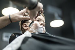 Humorous shaving of little boy. Thoughtful kid with a shaving foam on the face in the barbershop. He wears a black salon cape. Barber is shaving boy`s face with Royalty Free Stock Image