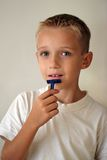 A humorous shot of a young boy shaving. And looking at the camera Royalty Free Stock Photography