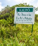 Humorous Road Sign Land of Rain That Makes One Hide Behind Rocks. Humorous sign in Hawaiian language along the road to Hana in Maui. Sign describes Kaupo as Land Royalty Free Stock Photography