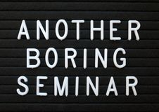 Humorous take on Seminars that are a waste of time. The words Boring Seminar in white plastic letters on a black letter board as a humorous reminder to provide Stock Photography