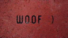 Humorous Wallpaper. `Woof :` Wallpaper and Background, with the whimsical utterance etched into red brick Royalty Free Stock Photography