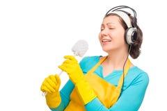 Humorystyczna fotografii gospodyni domowa z hełmofonami i cleaning muśnięciem Fotografia Royalty Free
