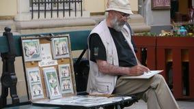Humour cartoonist in Budapest. BUDAPEST, HUNGARY - MAY 1, 2012 - Street cartoonist drawing stock photos