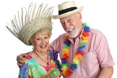 Humour On Holiday. An attractive elderly couple on a tropical vacation, laughing together.  Isolated Stock Images