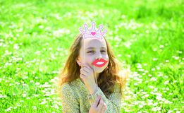 Humour queen concept. Girl sits on grass at grassplot, green background. Girl on cheerful face spend leisure outdoors. Child posing with cardboard smiling lips stock images
