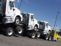 Humped Trucks. A brand new yellow truck transports an additional three new white units stock image