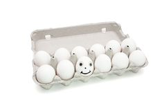 Humpty Dumpty egg in paper box. Funny egg with eyes among dozen in a paper box on white background Stock Photography