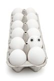 Humpty Dumpty egg in a paper box. Funny egg with eyes among dozen in a paper box on white background Royalty Free Stock Image