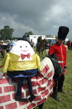 Humpty Dumpty Fancy dress parade. Humpty Dumpty sits astride a pony with a cloak that is made to look like a wall. The pony is being led by a man dressed as a Stock Images