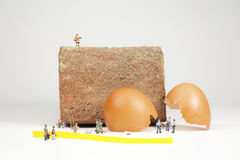 Humpty Dumpty was Pushed. Egg shell fragments of Humpty Dumpty next to a brick wall with miniature policemen, firemen and spectators investigating the crime of Royalty Free Stock Photography