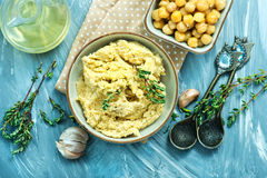 Humus. In bowl and on a table Stock Photography