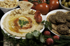 Humus and Falafels. Humus on plate with olives, chickpeas, radishes and tomatoes and falafwls Royalty Free Stock Images