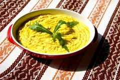 Humus paste with olive oil and chili,. Decorated with rucola Stock Photo