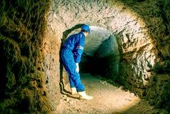 Hunched arbeider in blauwe algemene en veiligheidshelm in ondergrondse tunnel Gevaarlijke werkgelegenheid stock fotografie