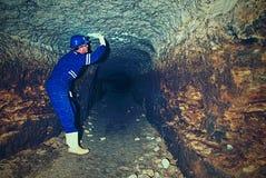 Hunched arbeider in blauwe algemene en veiligheidshelm in ondergrondse tunnel Gevaarlijke werkgelegenheid stock foto's