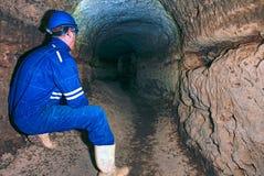 Hunched arbeider in blauwe algemene en veiligheidshelm in ondergrondse tunnel Gevaarlijke werkgelegenheid stock foto