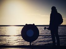 Hunched artist photograph with camera on tripod. Tourist at handrail. On mole take photos over sea to morning horizon. Tourist watch sun above smooth ocean royalty free stock photo