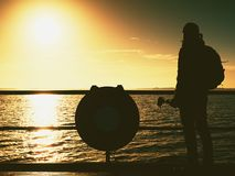 Hunched artist photograph with camera on tripod. Tourist at handrail. On mole take photos over sea to morning horizon. Tourist watch sun above smooth ocean royalty free stock photography