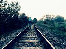 Hunched man is walking on railway in misty autumn day Royalty Free Stock Image