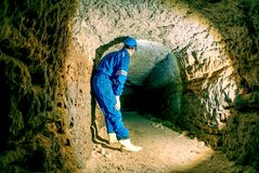 Hunched worker in blue overall and safety helmet in underground tunnel. Dangerous employment. Hunched worker in a blue overall and a safety helmet work in stock photography
