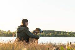 Hundägaren och hennes husdjur sitter på flodstranden på solnedgången arkivfoton