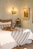 Hund, der am Fuß des Betts sitzt Lizenzfreies Stockbild
