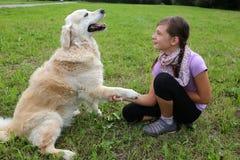 Hund, der Hände mit einem Kind rüttelt Stockfotos