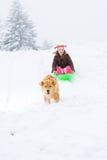 Hund, der Kind auf einem Schlitten zieht Lizenzfreies Stockfoto