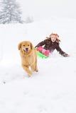 Hund, der Kind auf Schneeschlitten zieht Lizenzfreies Stockbild