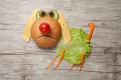 Hund gemacht vom Lebensmittel auf hölzernem Hintergrund Stockfotografie