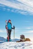 Hund i bergen i snön med husmor i alpin skidåkning Royaltyfri Bild