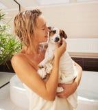 Hund neben der Frau im Badezimmer Stockbilder