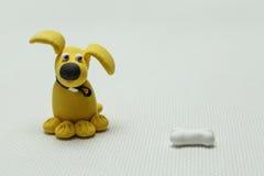 Hund och ett ben från plasticine Arkivbild