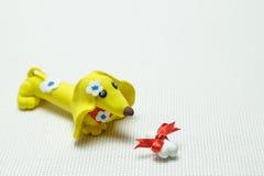 Hund och ett ben från plasticine som binds upp av en musikband Royaltyfria Bilder