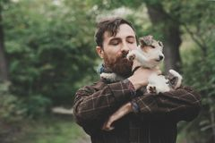 Hund och hans ägare - kall hund och unga mannen som har gyckel i en parkera - begrepp av kamratskap, husdjur, samhörighetskänsla Arkivfoto