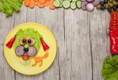 Hund som göras av nya grönsaker på plattan och trä Arkivfoton