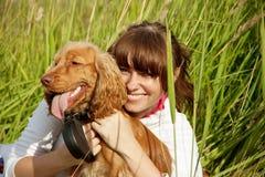 hund som omfamnar den lyckliga flickan henne som är ung Fotografering för Bildbyråer