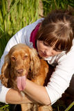 hund som omfamnar flickan henne ståendebarn Arkivbild