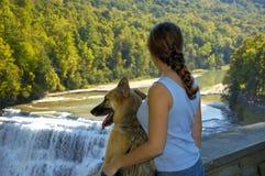 Hund und Mädchen am Wasserfall Stockbilder