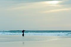 Hund und Mann, die ein Foto vor dem Meer machen Lizenzfreie Stockfotos