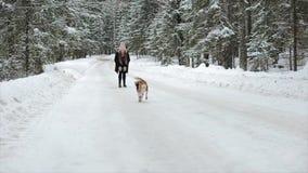 Hundbeaglet kör till och med snön Gulliga unga hipsterpar som har gyckel i vinter, parkerar med deras hund på en ljus dag och lager videofilmer