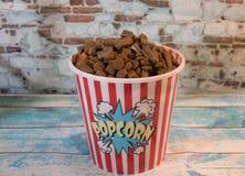 Hundbilliga prydnadssaker i en behållare av popcorn fotografering för bildbyråer