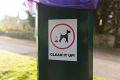 Hundeabfall räumen Zeichen auf Plastikabfalleimer auf lizenzfreies stockbild