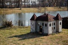 Hundehütte in Form eines Schlosses auf der Flussbank in einem Park stockbilder