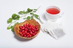 Hunderosafarbener Tee mit Früchten und grüner Niederlassung Stockbilder