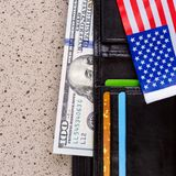 Hundert Dollar Banknote erreichen heraus aus einem schwarzen alten Geldbeutel heraus Lizenzfreie Stockbilder